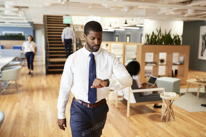Businessman Walking Through Modern Office Checking Health Data On Smart Watch