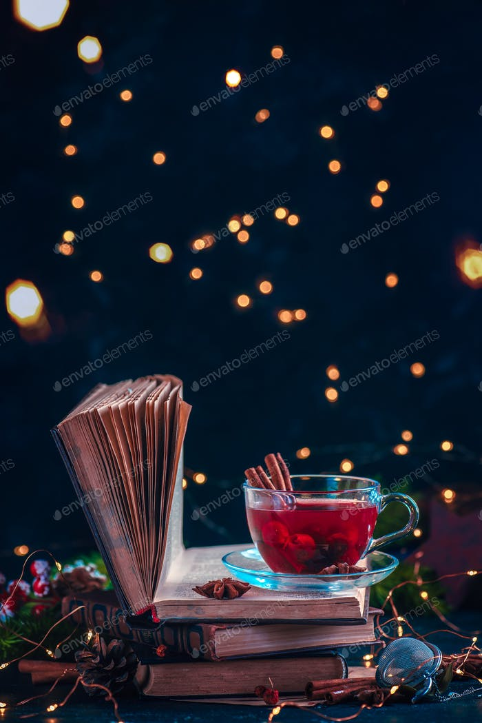 Red berry tea on a stack of books with fairy lights. Christmas drink on a dark background with copy