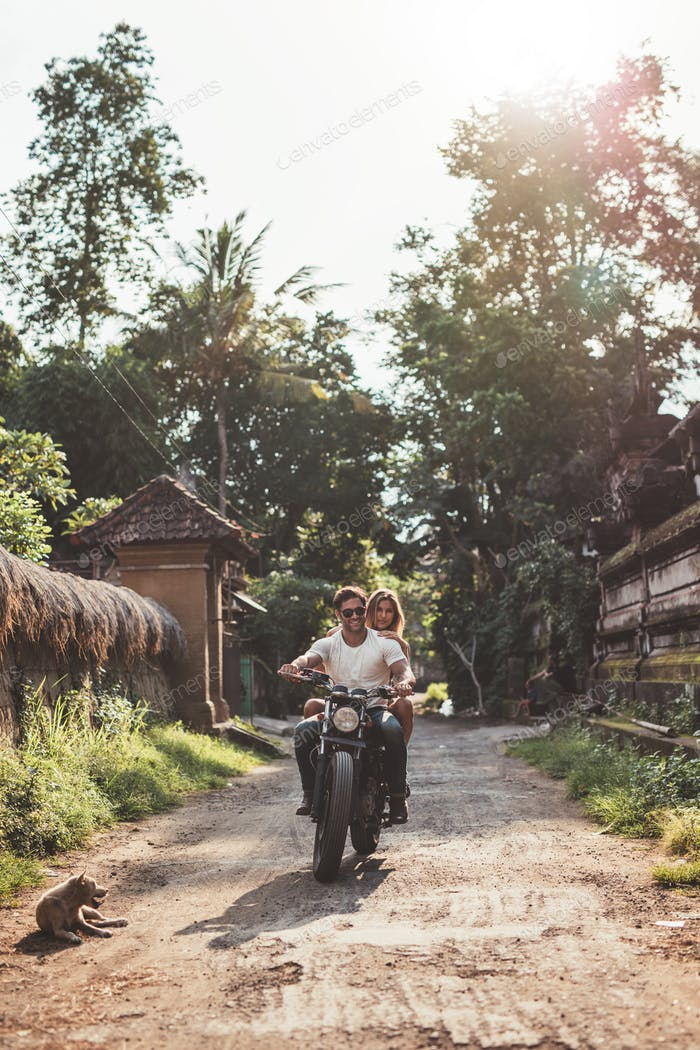 Couple enjoying motorcycle ride through a village road.
