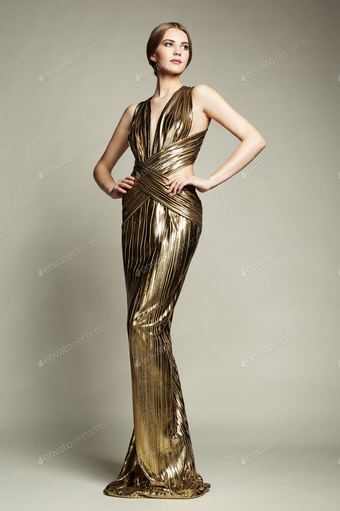 Fashion portrait of young beautiful woman in gold dress