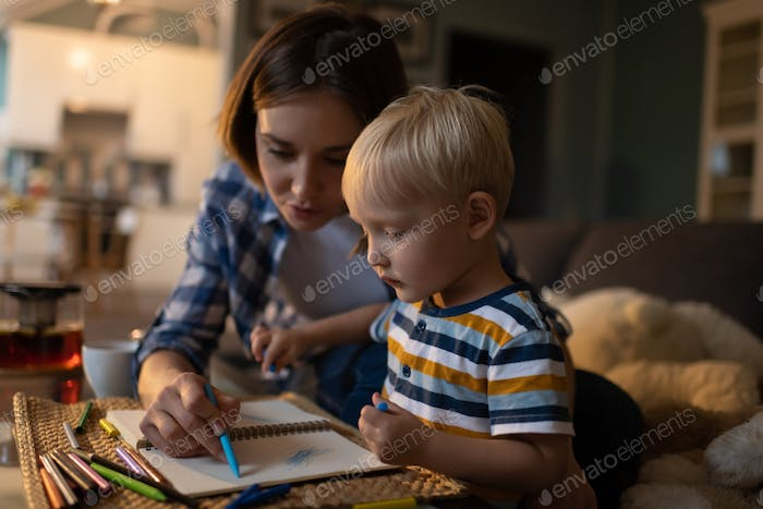 Mother spending time with little son and drawing at home
