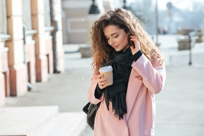 Young woman walking in the sunny city