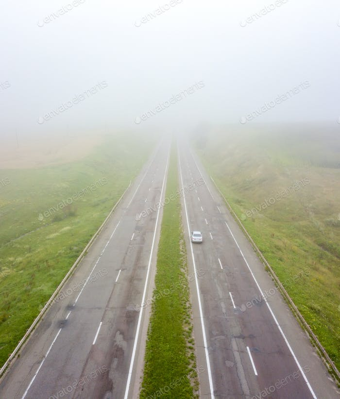 Aerial view of the road with a passing car and a field in the autumn, foggy morning. Photo from the