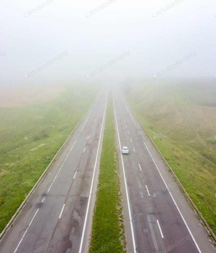Luftaufnahme der Straße mit einem vorbeifahrenden Auto und einem Feld im Herbst, nebligen Morgen. Foto aus dem