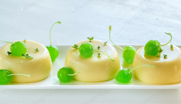 Vanilla puddings decorated with cocktail cherries