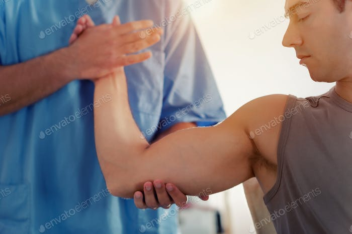 Physiotherapist Working With Patient Arm