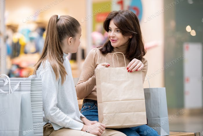 Young female with paperbag looking at her daughter while discussing purchase