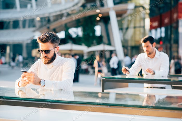 two handsome businessman using smartphone