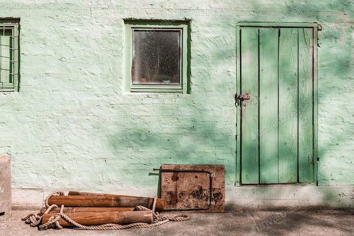 Old shed with brick wall painted in pale green