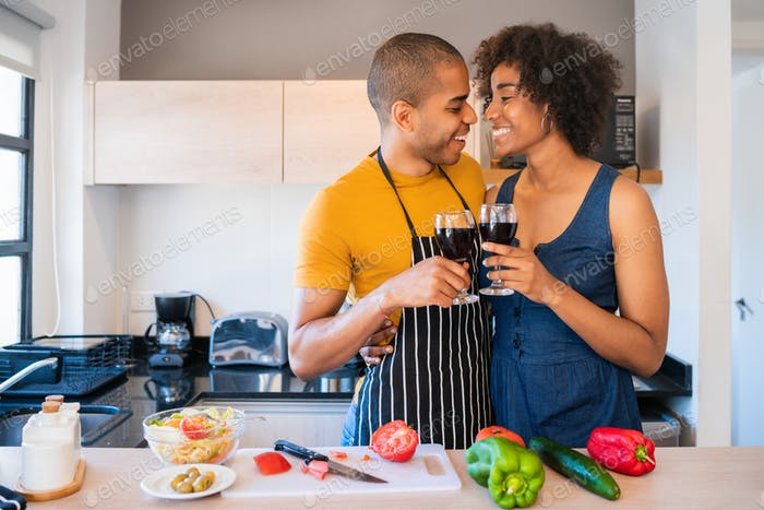Latin couple cooking together in the kitchen.