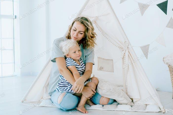 Mama umarmt ihre kleine entzückende Tochter. Zarte mütterliche Liebe.