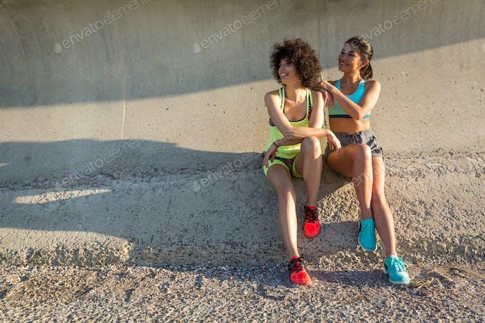 Two happy sporty women in sportswear sitting together