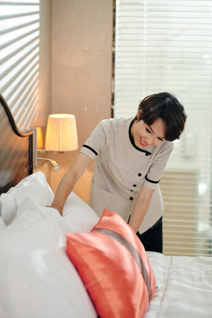 Maid putting pillows on bed