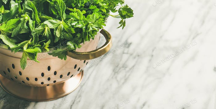 Bunch of fresh garden herbs in brass colander, copy space