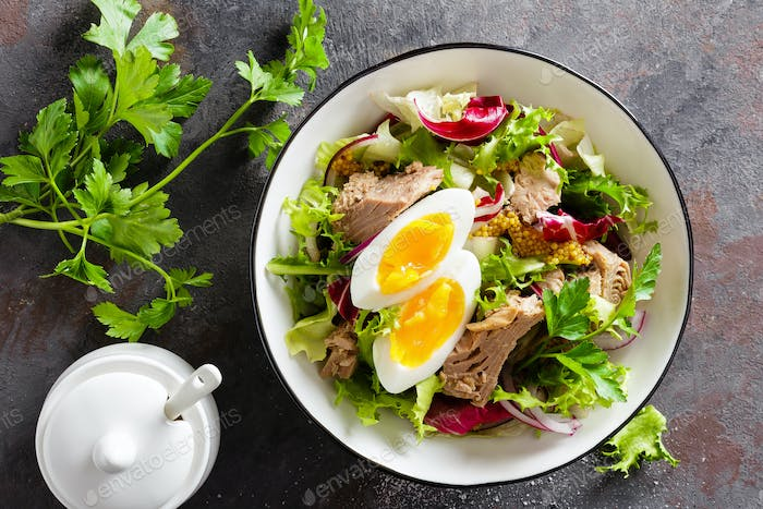 Diet food tuna salad with boiled egg, canned fish, onion and green lettuce top view