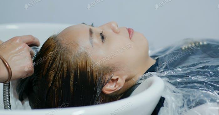 Woman wash her hair in salon