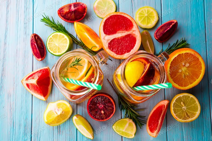 two glasses of citrus lemonade and a slice of fruit on a blue background