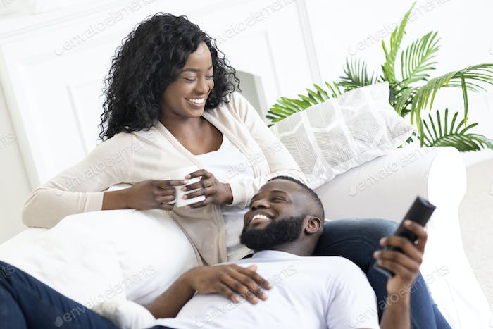 Black family couple relaxing on sofa, spending time at home