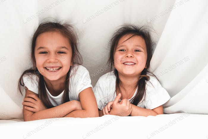 two girls reading under blanket
