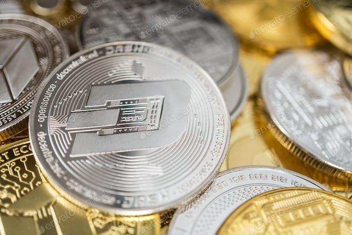 Nahaufnahme von Dash Physical Coin auf Stapel vieler anderer Kryptowährungen