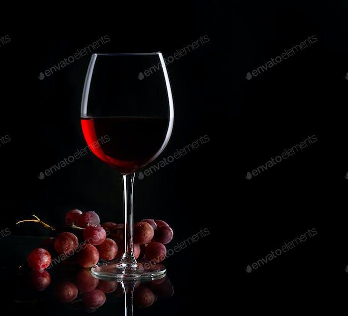 Glas Rotwein und Trauben auf dem dunklen Hintergrund