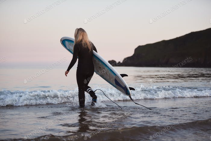 Woman Wearing Wetsuit Carrying Surfboard As She Walks Into Sea