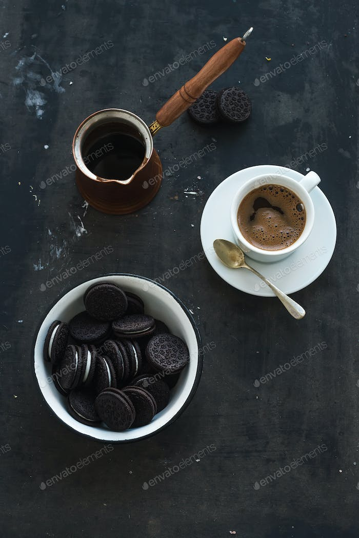 Chocolate cookies with cup and pot of coffee, dark grunge backdrop