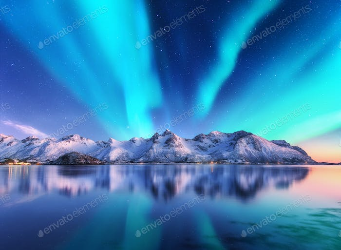 Northern lights and snow covered mountains in Lofoten islands, Norway