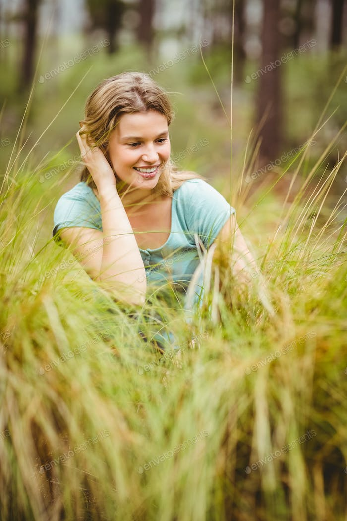 Young pretty hiker sitting in the high grass in the nature