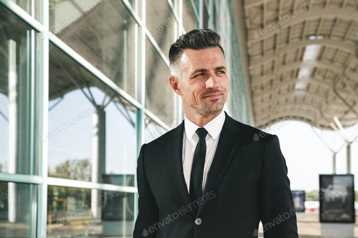 Smiling businessman dressed in suit walking outside airport
