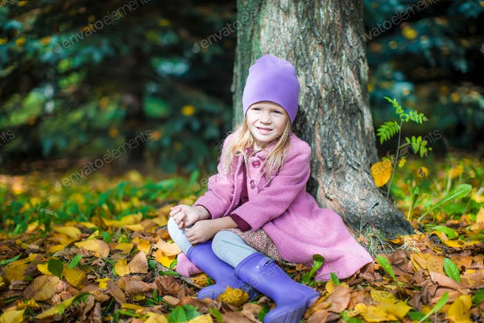 Little happy girl in autumn park on sunny fall day