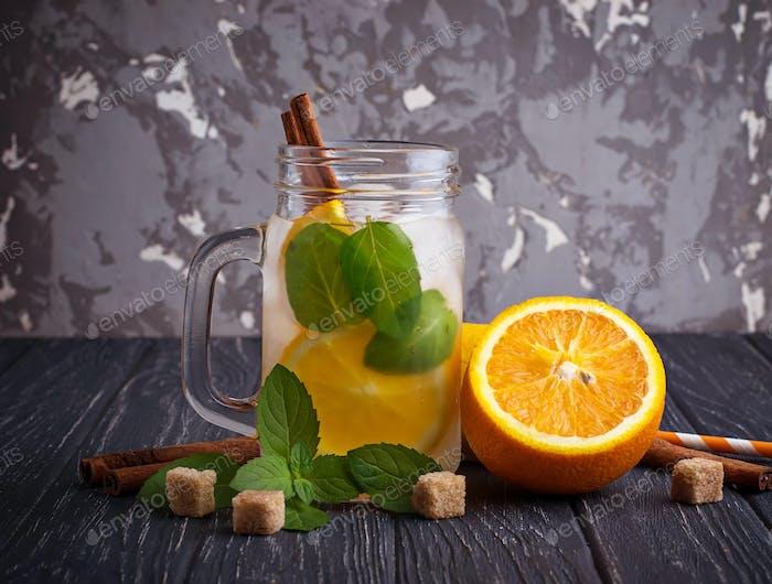 Detox water with orange, mint and cinnamon in jar