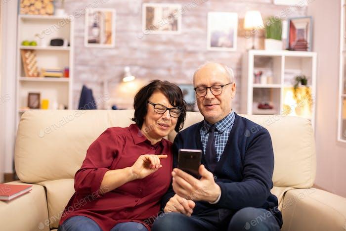 Schöne ältere paar nehmen ein selfie während sitzen auf der couch