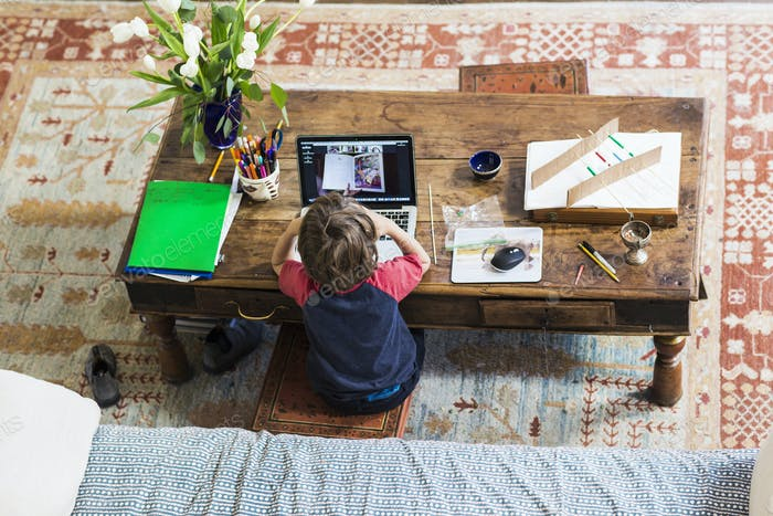 over head view of young boy attending remote schooling class at home
