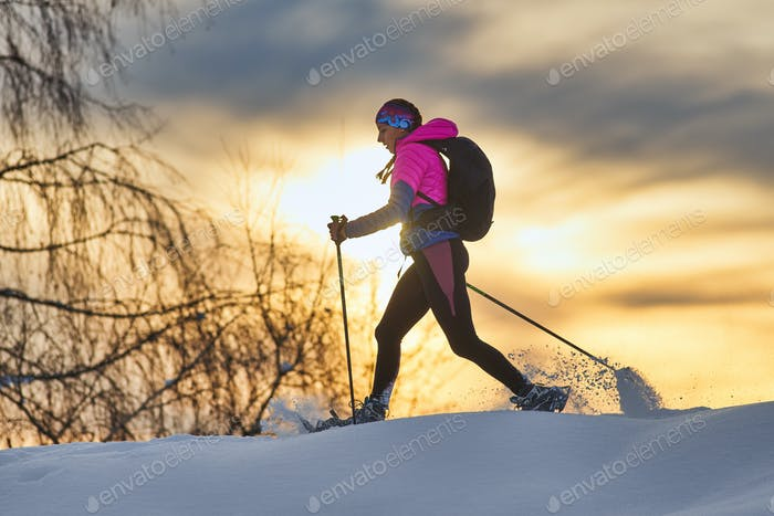 Lonely girl hike with snowshoes