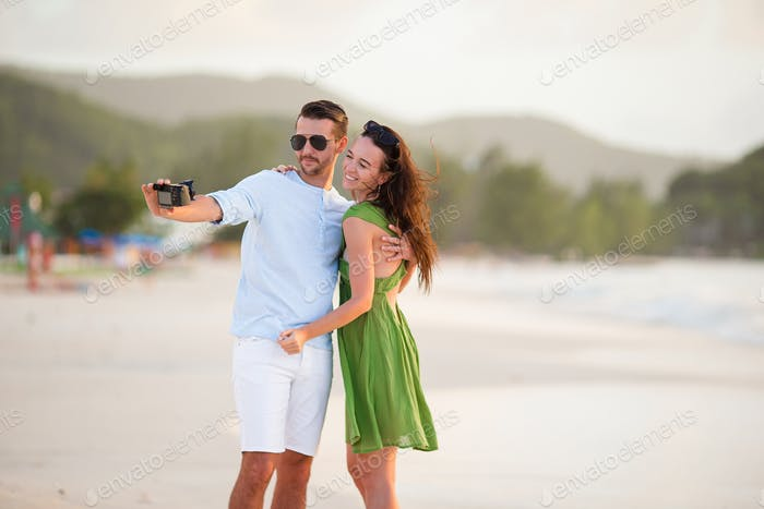 Happy couple taking a photo on white beach on honeymoon holiday