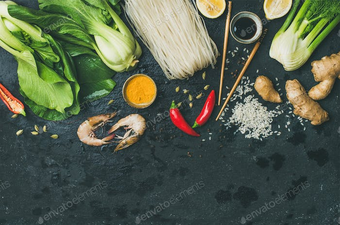 Flat-lay of Asian cuisine ingredients over black background, copy space