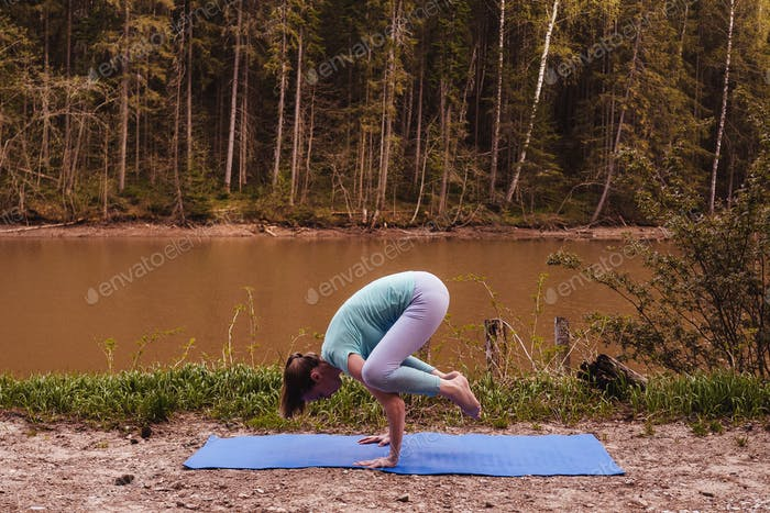 Young woman making yoga near river, evening.