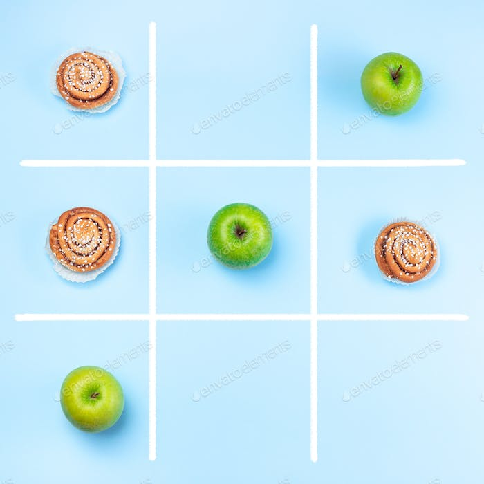 Green apples vs cinnamon buns in tic tac toe or noughts and crosses game