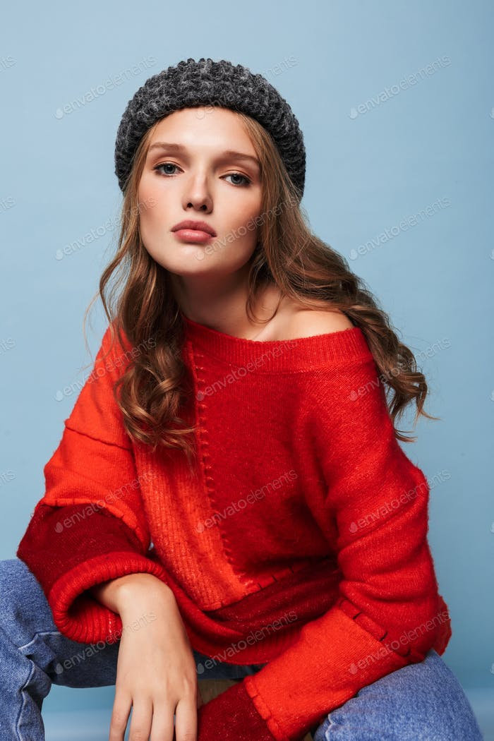 Young beautiful pensive woman with wavy hair in hat and red sweater thoughtfully looking in camera