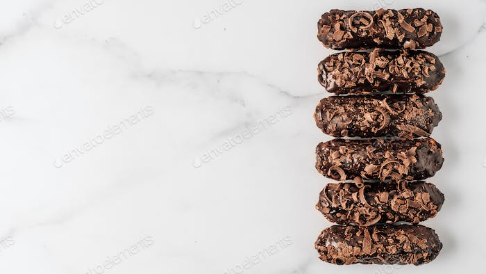 Healthy chocolate eclairs on marble background