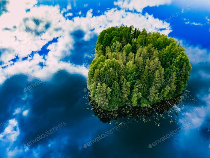 Aerial view over the small green forest island in blue lake in Finland