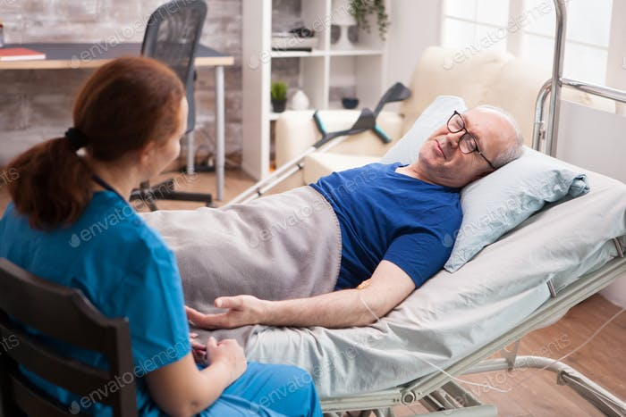 Male pensioner in nursing home talking with female doctor