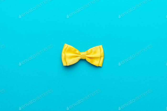 Minimalist Photo Of Yellow Bow Tie On Turquoise Blue Background And Copy Space