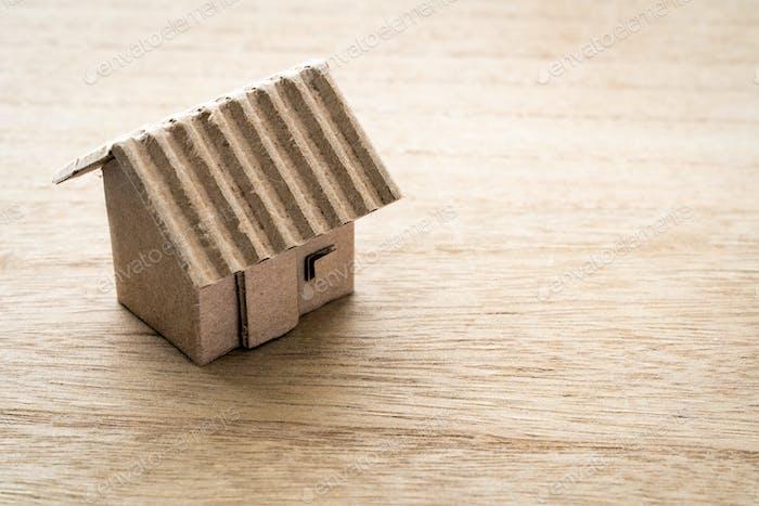 Modell des Kartonhauses auf hölzernem Hintergrund