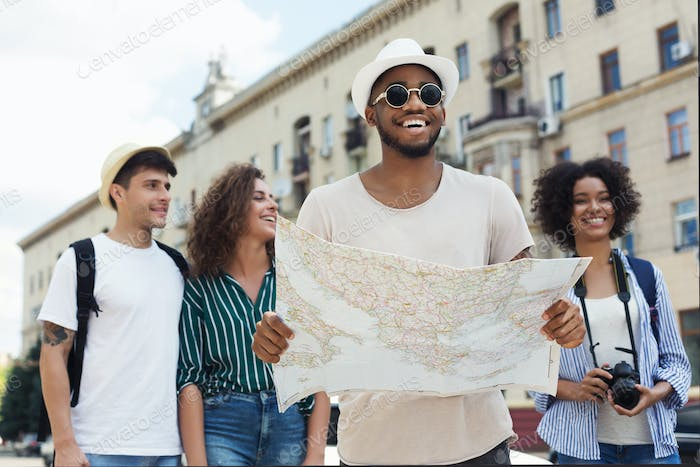 Happy hipsters using navigation map to explore the city
