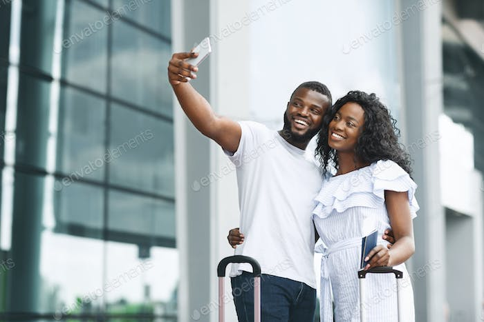 Happy african couple taking selfie, waiting for flight near airport