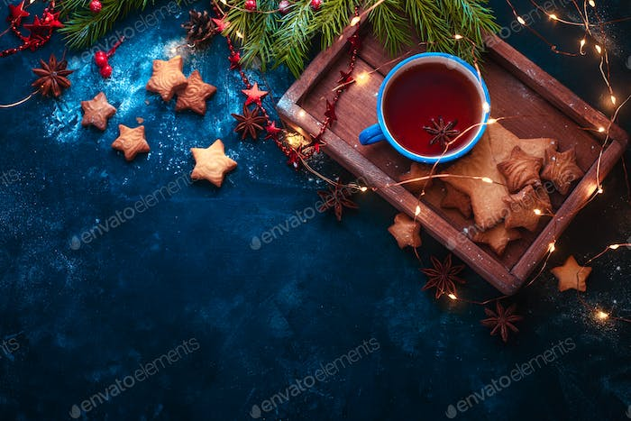 Cookies, tea and fairy lights flat lay with fir tree branches, wooden tray, anise stars, and