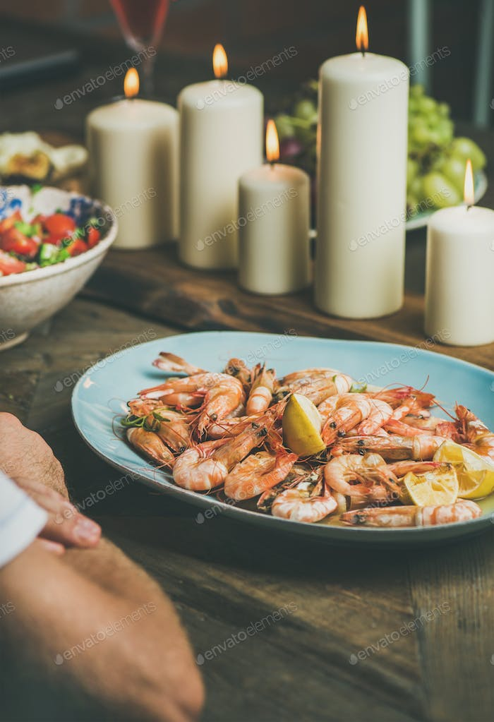 Salad, shrimps and candles on wooden table