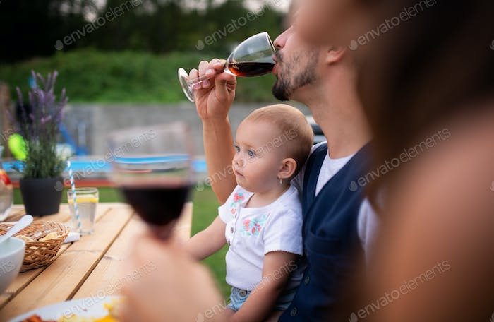 Young couple with baby sitting at table outdoors on family party, drinking wine